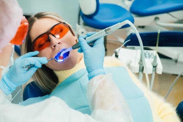 Una hermosa joven con gafas dentales trata sus dientes en el dentista con luz ultravioleta. relleno de dientes.