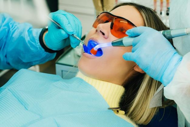 Una hermosa joven con gafas dentales trata sus dientes en el dentista con luz ultravioleta