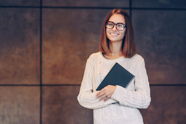Hermosa joven con gafas elegantes y un suéter blanco cálido con cuaderno de bocetos de un muro de hormigón