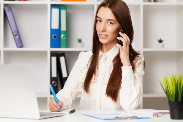 Hermosa joven gerente mujer hablando por teléfono mientras trabajaba en la computadora portátil en la oficina