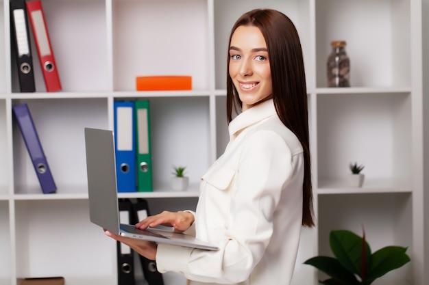 Hermosa joven gerente mujer trabajando con documentos en la oficina