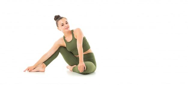 Una hermosa joven gimnasta con cabello largo y oscuro peinado en un paquete con un traje elástico deportivo verde se sienta y sonríe.