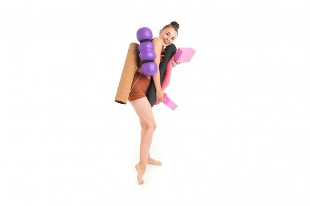Hermosa joven gimnasta con cabello largo y oscuro relleno en un paquete en traje elástico deportivo marrón con inventario deportivo