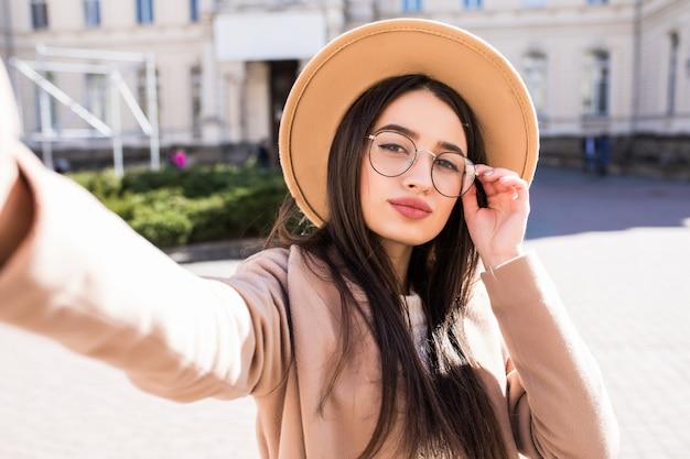 Hermosa joven hace selfie en su nuevo teléfono inteligente al aire libre en la ciudad en un día soleado