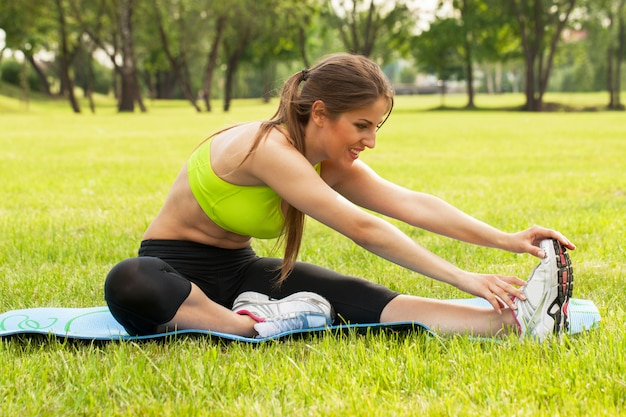 Hermosa joven haciendo ejercicio en un césped