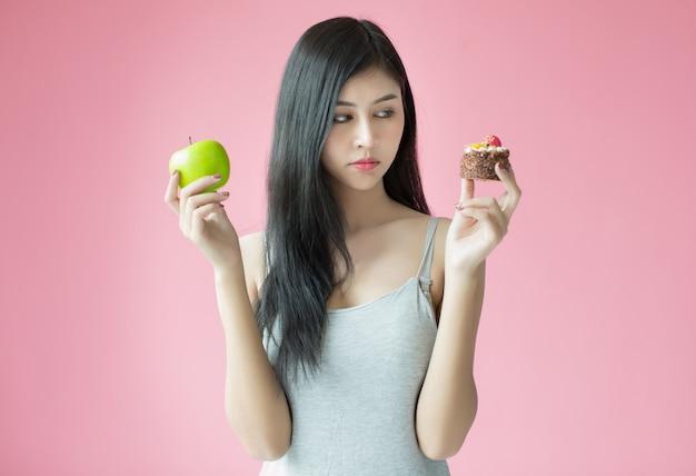 Hermosa joven haciendo una elección entre un pastel y una manzana