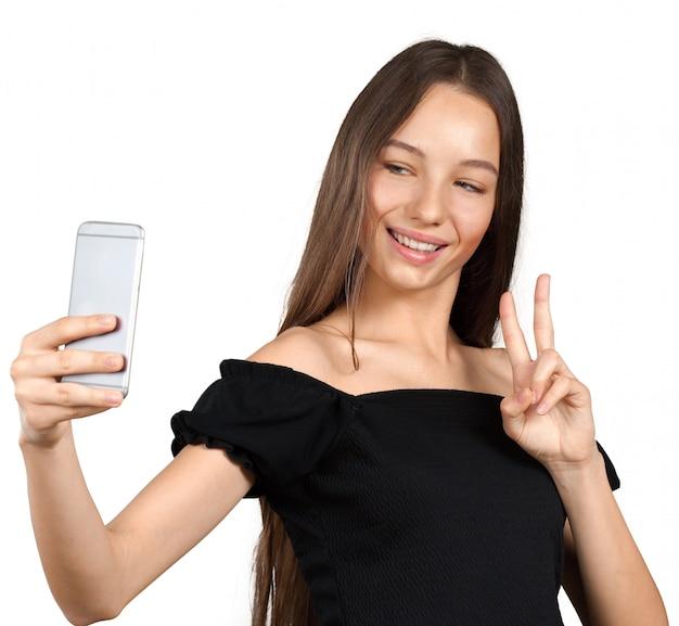 Hermosa joven está haciendo foto selfie con smartphone