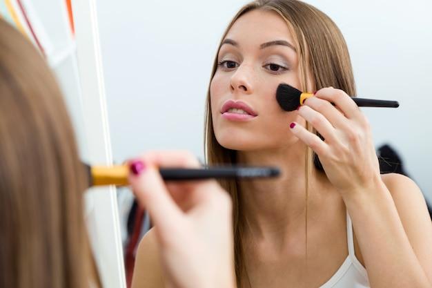 Hermosa joven haciendo maquillaje cerca de espejo en casa.