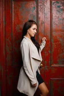 Hermosa joven en un impermeable cerca de la puerta roja cutre vintage