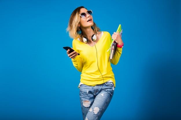 Hermosa joven inconformista sosteniendo libros y mirando smartphone