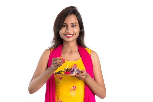 Hermosa joven india sosteniendo pooja thali o realizar adoración en blanco