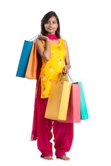 Hermosa joven india sosteniendo y posando con bolsas de compras sobre un fondo blanco.