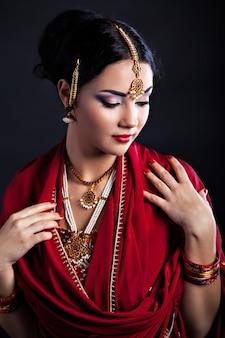 Hermosa joven india en vestimentas tradicionales y accesorios indios