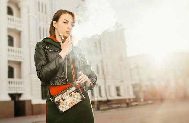 Hermosa joven inhalando humo. chica joven vaping contra el fondo de la ciudad.