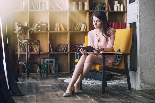 Hermosa joven inteligente se sienta con el libro electrónico en la biblioteca en una silla