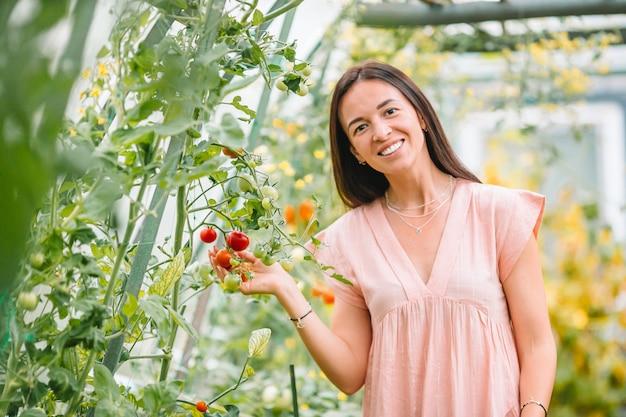 Hermosa joven jardinería en invernadero