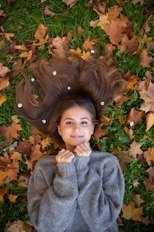 Hermosa joven con largo cabello natural en el suelo entre las hojas amarillas en un parque de otoño