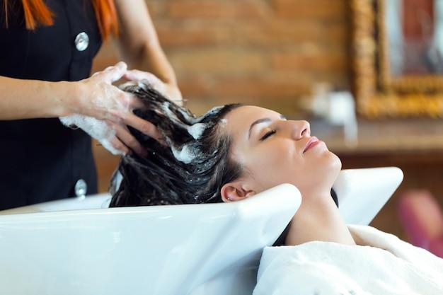 Hermosa joven lava el cabello en un salón de belleza.