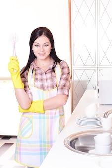 Hermosa joven lavando platos en la cocina