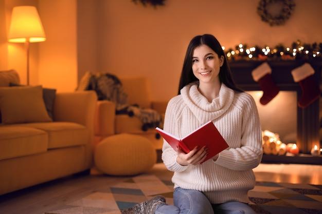Hermosa joven leyendo el libro en casa en la víspera de navidad