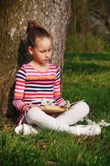 Hermosa joven está leyendo un libro en el parque, sentado en el césped cerca del árbol
