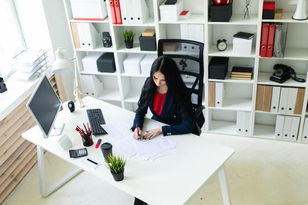 Hermosa joven llena los documentos, sentada en la oficina en la mesa