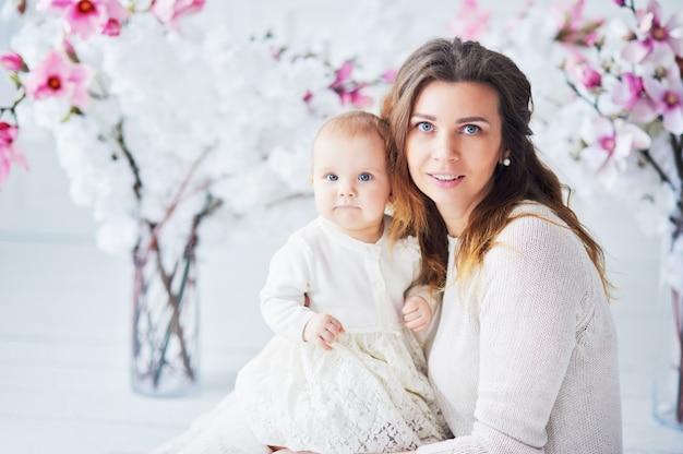 Hermosa joven madre con un bebé en sus brazos está de pie
