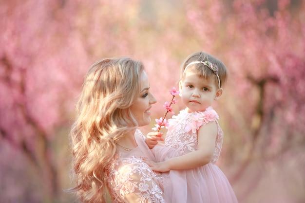 Hermosa joven madre con cabello blanco en el jardín con árboles rosados con su bebé en brazos