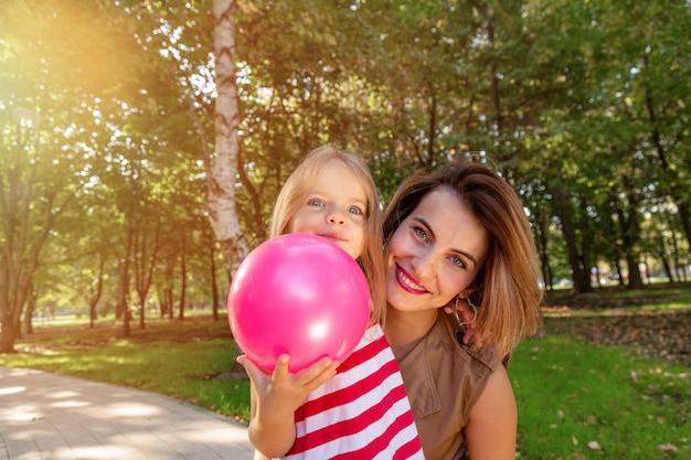 Hermosa joven madre e hija en un cálido día soleado de verano.