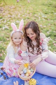 Hermosa joven madre e hija pequeña cerca de una magnolia floreciente. pascua de resurrección. primavera. flores rosas.