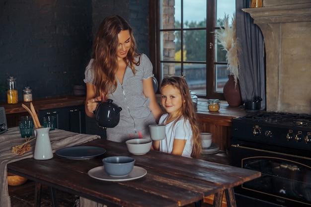 Hermosa joven madre jugando y divirtiéndose con su pequeña hija linda en el oscuro interior de la cocina en casa