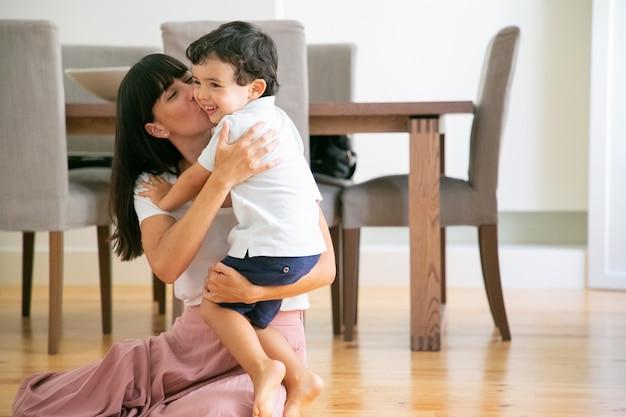 Hermosa joven madre sentada en el suelo y besando a su hijo.