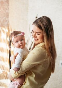 Hermosa joven madre sostiene a una pequeña hija en la habitación
