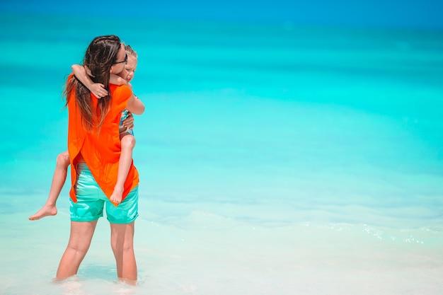 Hermosa joven madre y su adorable hijita se divierten en la playa tropical