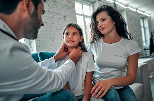 Hermosa joven madre y su pequeña hija en casa. el doctor está examinando al pequeño paciente.