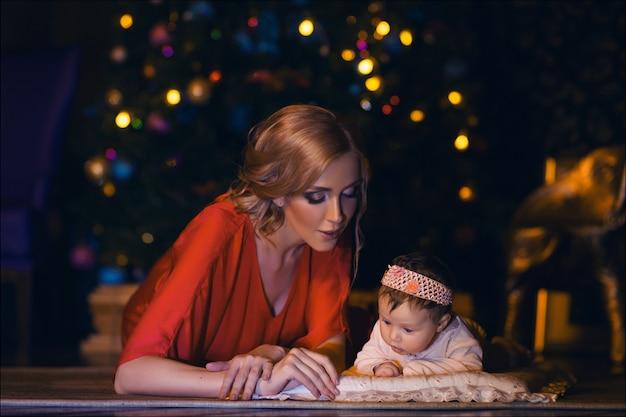 Hermosa joven madre en traje rojo posando con su lindo bebé