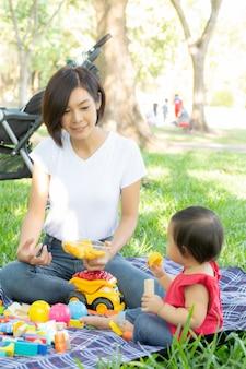 Hermosa joven mamá asiática e hija jugando bloques de juguete