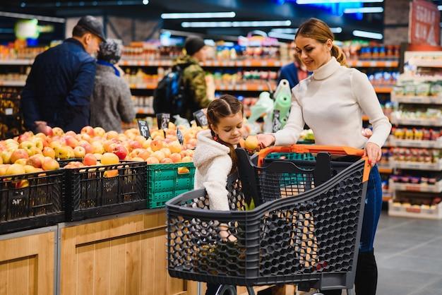 Hermosa joven mamá y su pequeña hija sonriendo y comprando comida