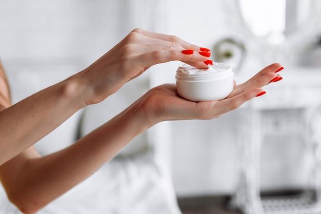 Hermosa joven manos sosteniendo un tarro de crema, aislado en un fondo blanco.