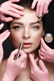 Hermosa joven con maquillaje natural nude con herramientas cosméticas en manos, rostro de belleza,