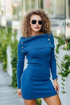 Hermosa joven con maquillaje perfecto, labios rojos, con un vestido azul, posando junto a la pared de cristal del centro comercial.