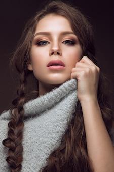 Hermosa joven con maquillaje suave en suéter cálido y cabello largo y liso