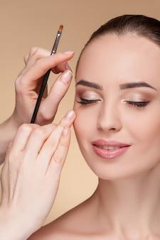 Hermosa joven se está maquillando en el salón de belleza