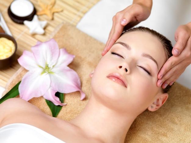 Hermosa joven con masaje spa de la cabeza en salón de belleza - en el interior