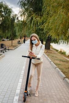 Hermosa joven en una máscara a caballo en el parque en un scooter eléctrico en un cálido día de otoño y hablando por teléfono. caminar en el parque.