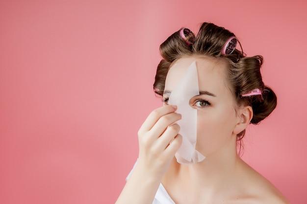 Hermosa joven con una máscara y rulos tocando su rostro.
