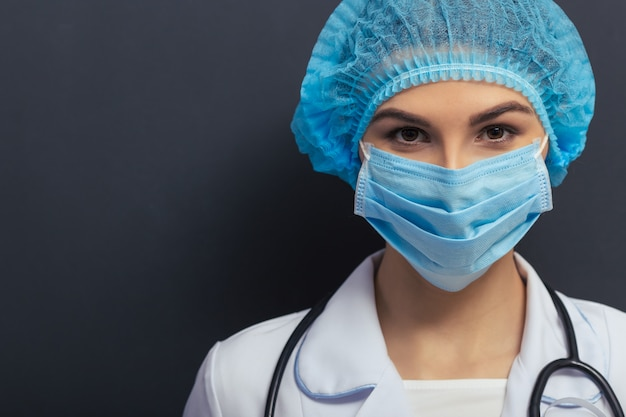 Hermosa joven médico en bata médica blanca.