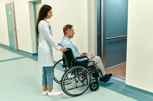 Hermosa joven médico con su paciente anciano discapacitado en silla de ruedas se acercó al ascensor de un hospital moderno.