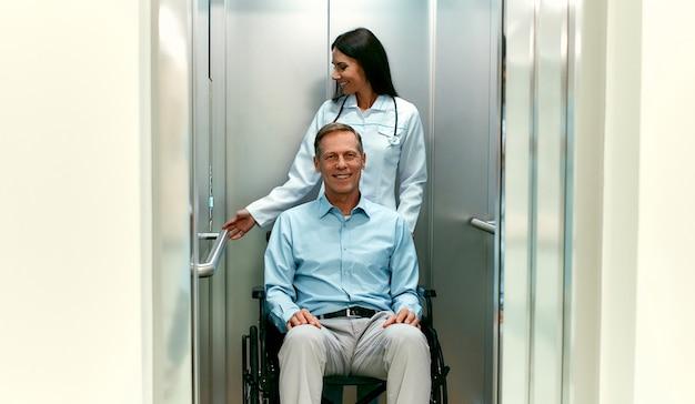 Hermosa joven médico con su paciente anciano discapacitado en silla de ruedas entró en el ascensor de un hospital moderno.