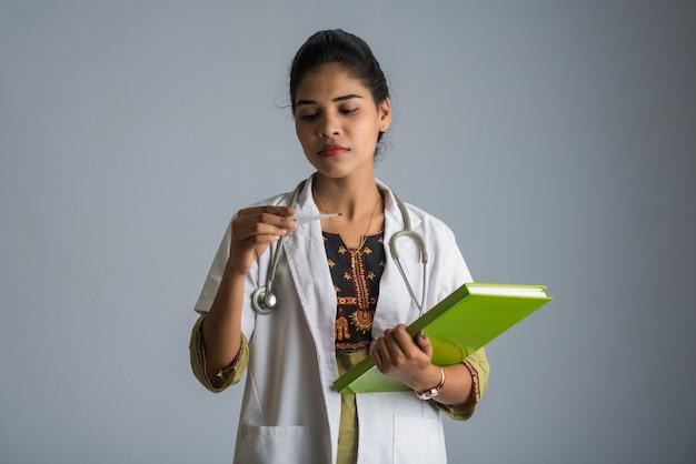 Hermosa joven médico con termómetro e informe o libro